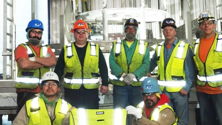 Picture of seven PIC employees in hard hats and safety vests, with two in front holding a safety vest with the PIC logo